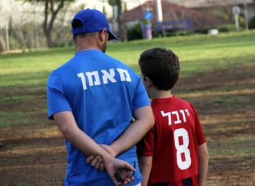 אימון כדורגל לילדים על דשא סינטטי עם מאמן מקצועי